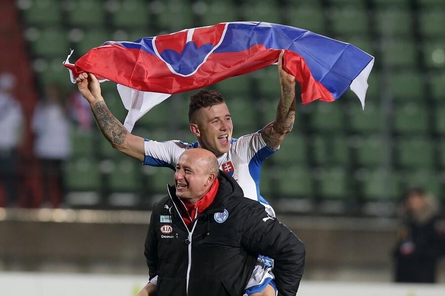 Slovakiens tränare firar med en spelare på ryggen och slovakiska flaggan